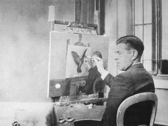 René Magritte fotografiado frente a uno de sus cuadros.